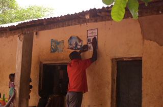 Setting of a Poster on the house wall of the village leader, Guinea Bissau Cacheu MPA